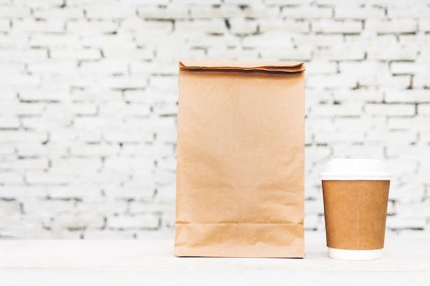 Tasse de café et sac en papier blanc avec espace de copie pour votre marque sur table