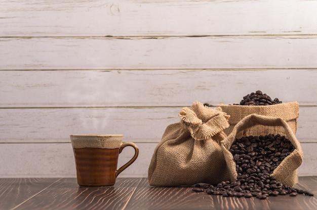 Tasse à café et sacs sur fond de bois clair