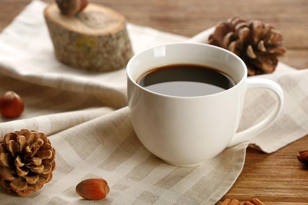Tasse de café sur une serviette sur fond de bois