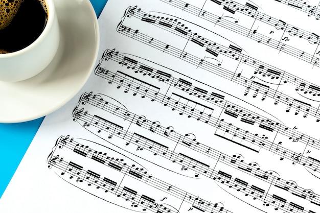 Tasse à café sur une soucoupe blanche et une feuille avec des notes de musique sur un bleu