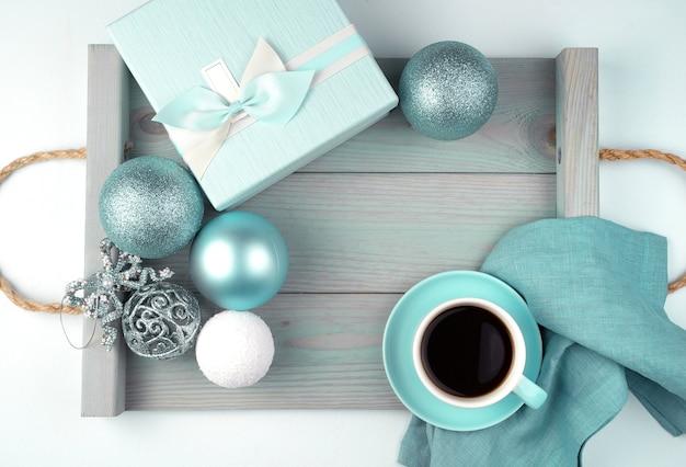 Une tasse de café sur une soucoupe, une boîte-cadeau et des boules de noël sur un plateau