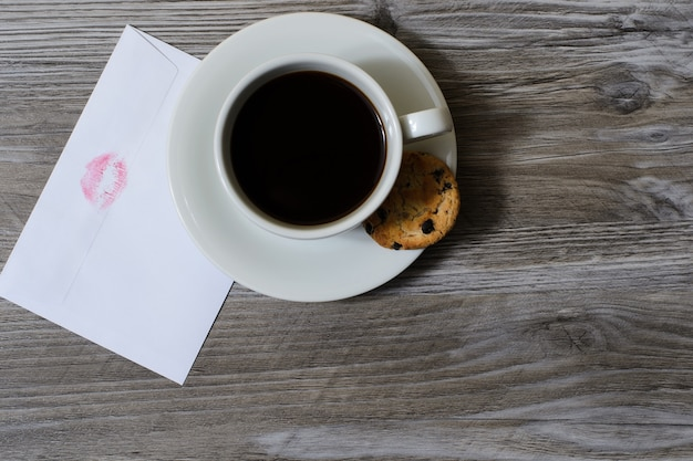 Tasse de café sur soucoupe avec enveloppe blanche de biscuits au chocolat avec impression des lèvres