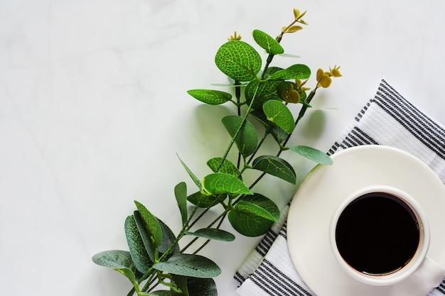 Tasse de café avec soucoupe, napery, bouquet de feuilles sur fond de marbre blanc