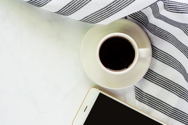 Tasse de café avec soucoupe, napery et smartphone sur fond de marbre blanc