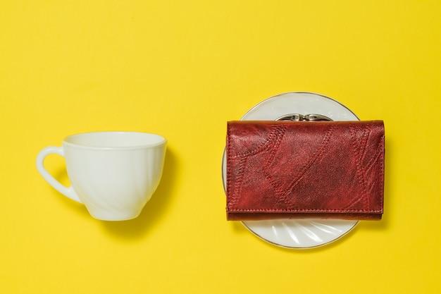 Une tasse de café, une soucoupe et un sac à main rouge sur fond jaune. café et argent.