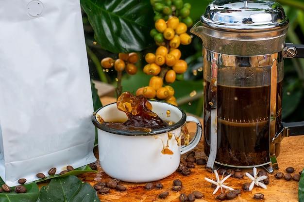 Tasse à café splash avec cafetière française avec emballage sans marque dans la forêt