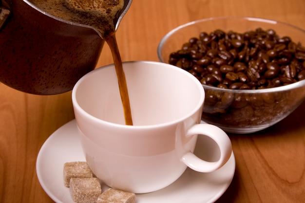 Tasse de café, sucre et haricots dans un bol en verre sur une table en bois