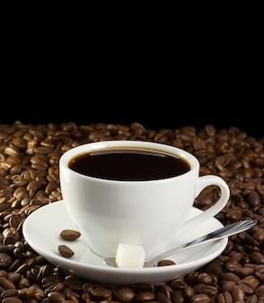 Tasse de café et de sucre sur les haricots isolés sur fond noir