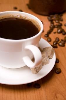 Tasse de café, sucre et haricots sur table en bois