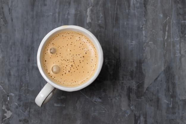 Une tasse de café sur une surface en céramique grise