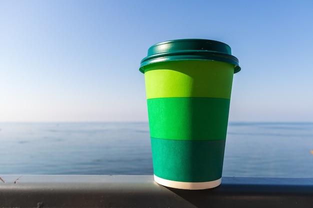 Tasse de café sur une table au-dessus du ciel bleu et de la mer vide au bord de la plage. concept de vacances d'été. maquette, espace de copie