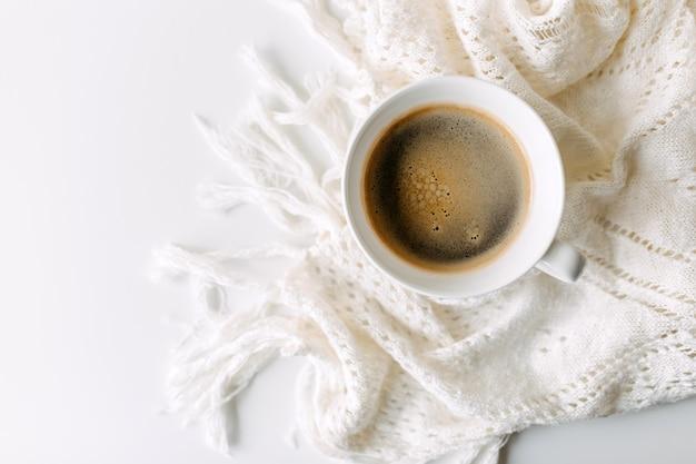 Tasse de café sur table blanche avec une couverture au crochet