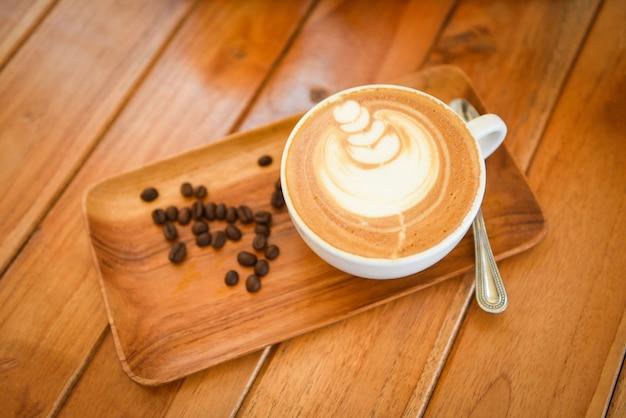 Tasse à Café Sur Table En Bois Au Café Avec Fond De Grains De Café, Cappuccino Ou Café Au Lait Photo Premium