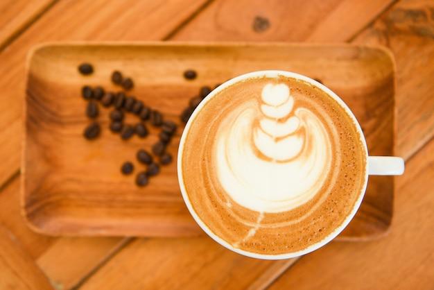 Tasse à café sur table en bois au café avec fond de grains de café, cappuccino ou café au lait