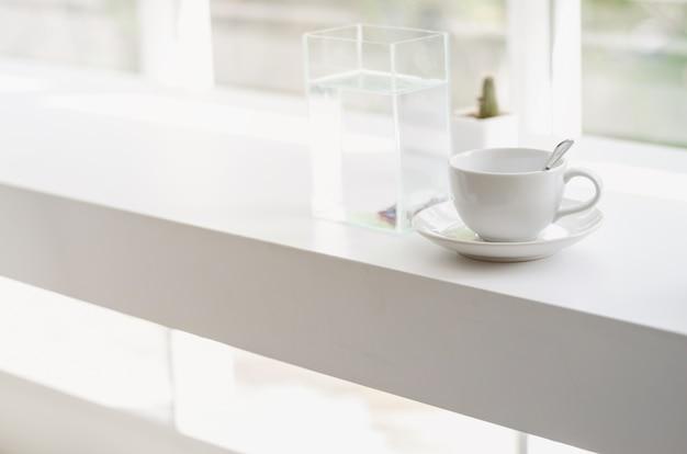 Tasse de café sur une table en bois blanc près d'une porte avec lumière chaude et fond de cactus floue