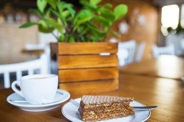 Tasse à café sur table en bois, gaufrette sucrée sur une assiette. fermer.