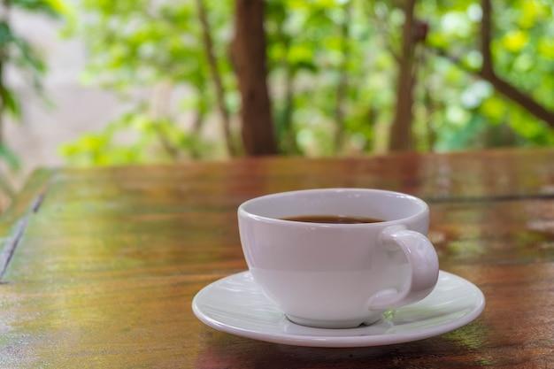 Une tasse de café sur une table en bois le matin avec la lumière du soleil en fin de matinée. une tasse de café sur une table en bois le matin avec la lumière du soleil en fin de matinée.