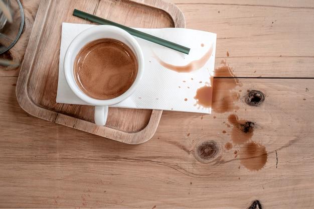 Tasse de café sur une table en bois avec des taches de café.