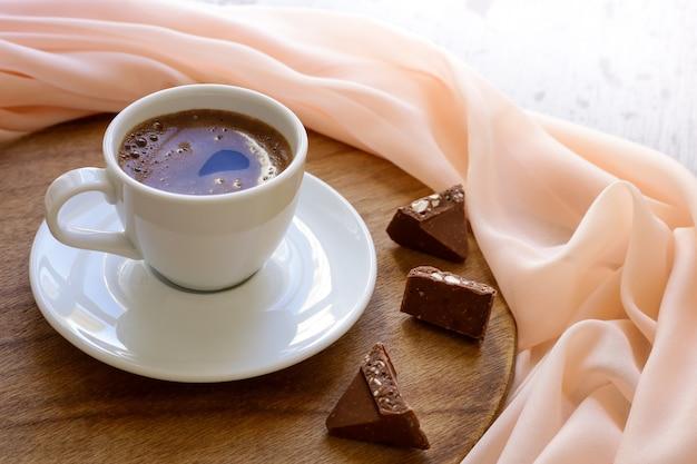 Tasse à café sur table en bois et tissu beige