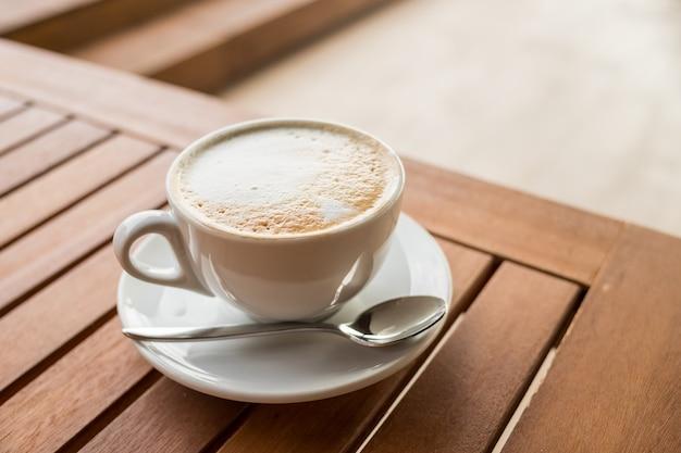 Tasse de café sur table avec cuillère et assiette