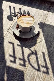 Une tasse de café sur la table et des grains de café wi-fi gratuit
