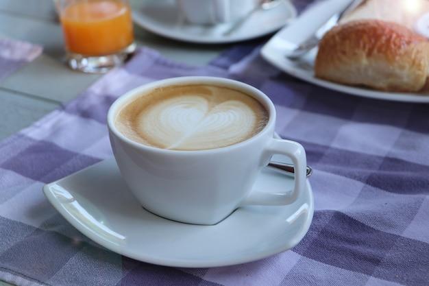 Une tasse de café sur la table avec une serviette, un cappuccino chaud avec de la mousse de lait cuit à la vapeur