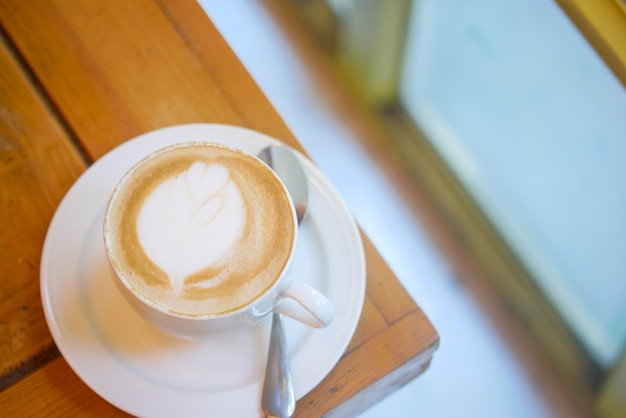 Une tasse de café tardif avec un design en forme de fleur sur le dessus du café