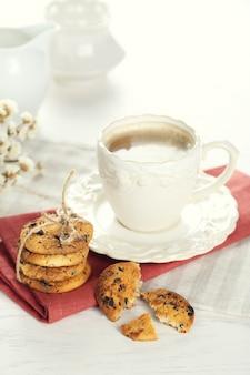 Tasse de café et tas de délicieux biscuits avec des miettes de chocolat sur une table en bois blanc