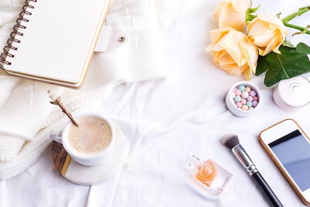 Une tasse de café, téléphone et cahier, roses et cosmétiques