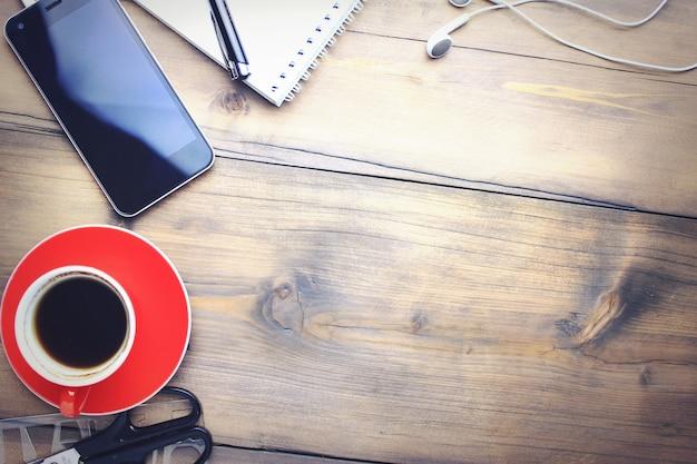 Tasse de café, téléphone, écouteur, cahier et stylo sur bois