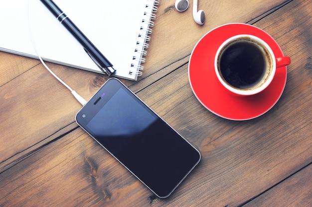 Tasse de café, téléphone, écouteur, cahier et stylo sur table en bois