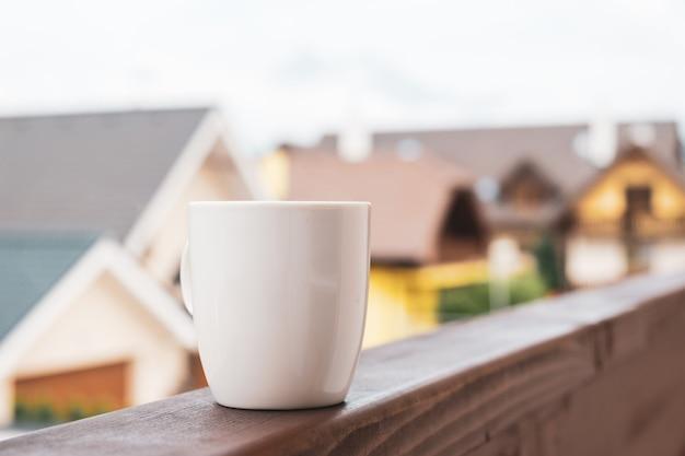 Une tasse de café ou de thé chaud sur le balcon avec des maisons