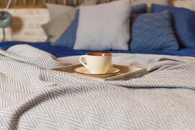 Tasse à café ou thé chaud le matin sur le lit. couverture beige, oreillers gris et bleus sur lit en bois. intérieur scandinave.