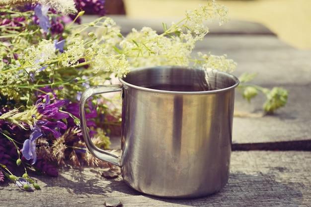 Une tasse de café ou de thé avec des fleurs est sur la table
