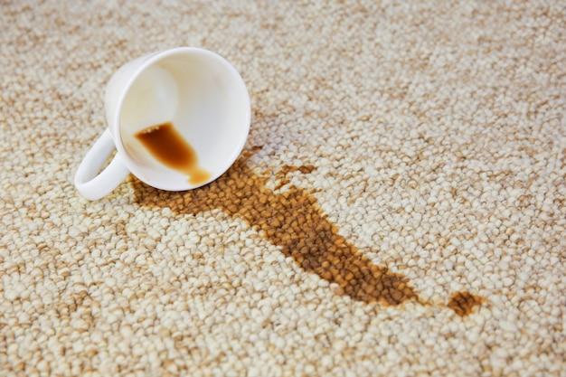 Tasse de café tombée et tapis taché