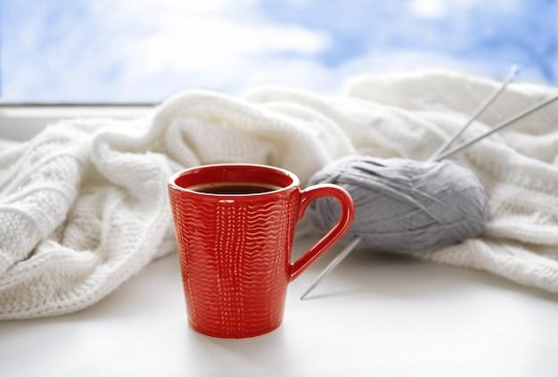 Tasse de café et tricot sur le rebord de la fenêtre