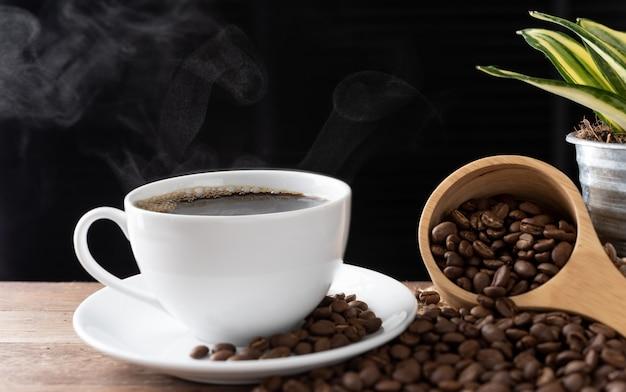 Tasse de café à la vapeur avec des grains torréfiés et un pot de fleurs sur fond de bois au soleil du matin