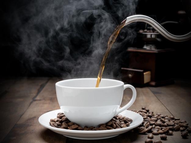 Tasse à café à vapeur avec moulin, beens, bouilloire et tasse en verre sur fond sombre de table en bois grunge