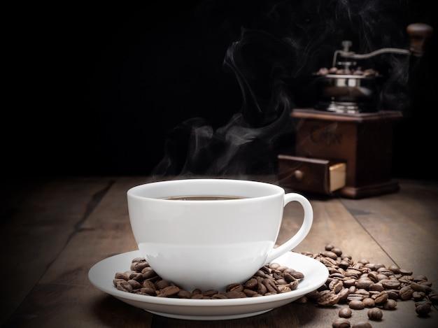 Tasse à café à vapeur avec moulin, beens et tasse en verre sur fond sombre de table en bois grunge