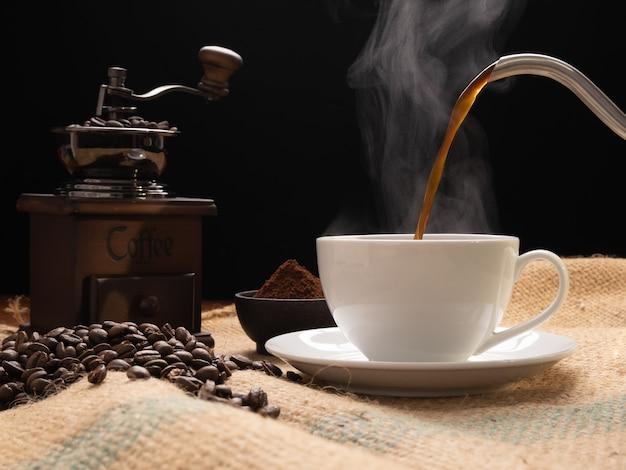 Tasse à café vapeur avec moulin, beens torréfiés, café moulu et bouilloire sur toile de jute sur fond de table en bois grunge