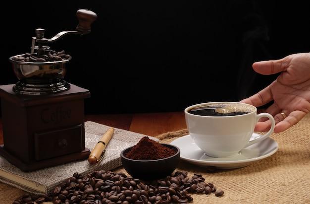 Tasse de café vapeur versant à la main avec moulin, grains torréfiés, café moulu et bouilloire sur toile de jute sur fond de table en bois grunge