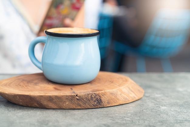 Tasse à café en verre bleu sur plaque de bois