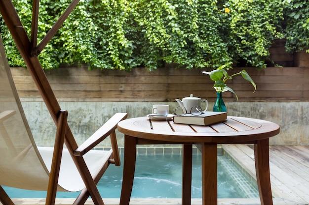 Tasse de café et de verres en lisant un livre avec une plante verte en arrière-plan.
