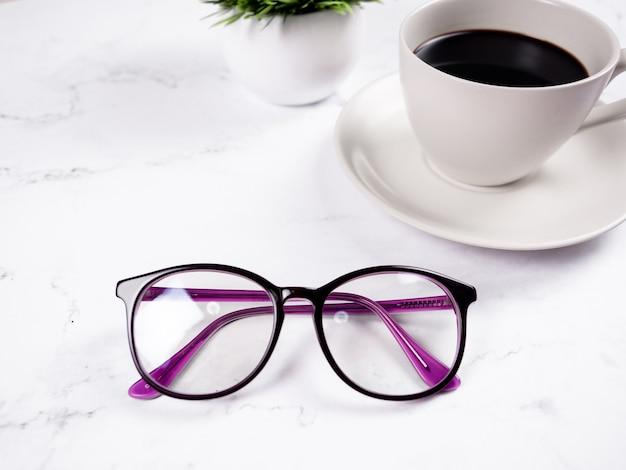 Tasse de café de verres de plan rapproché avec le vase de fleur sur le matin d'espace de copie de fond de table de marbre
