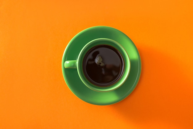 Tasse de café vert sur fond orange
