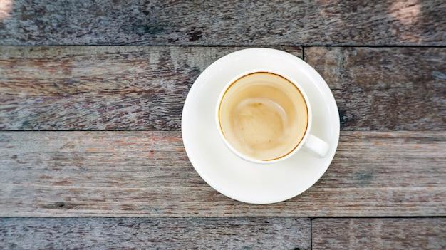 Tasse à café vide après boisson sur une table en bois.