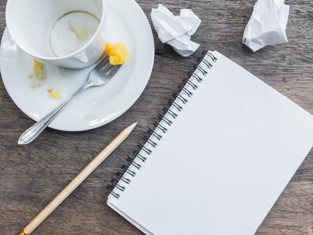 Tasse de café vide et assiette avec le bloc-notes