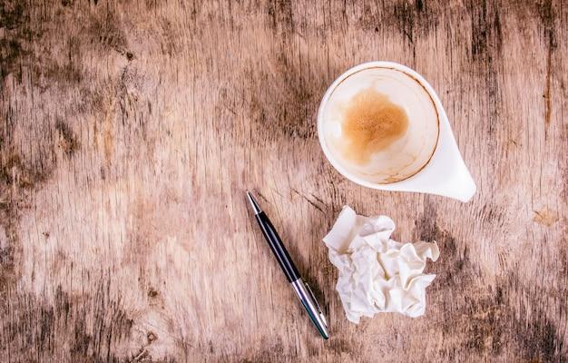 Tasse à café vide, feuille de papier froissé et stylo sur table en bois