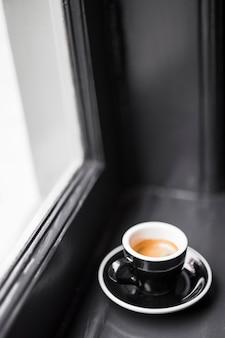 Tasse à café vide noire avec des taches de café sur le rebord de la fenêtre