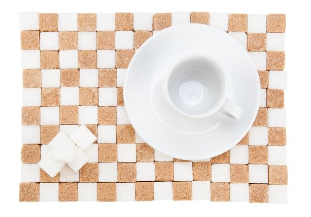 Tasse à café vide sur une soucoupe avec quatre cubes de sucre blanc sur un support de sucre blanc et brun. mise à plat